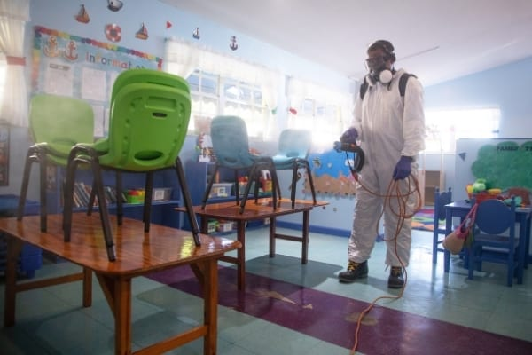 Suited man disinfects classroom. Deep cleaning service Cambridge anticovid-19
