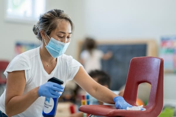 Lady cleans and disinfects classroom in Cambridge.