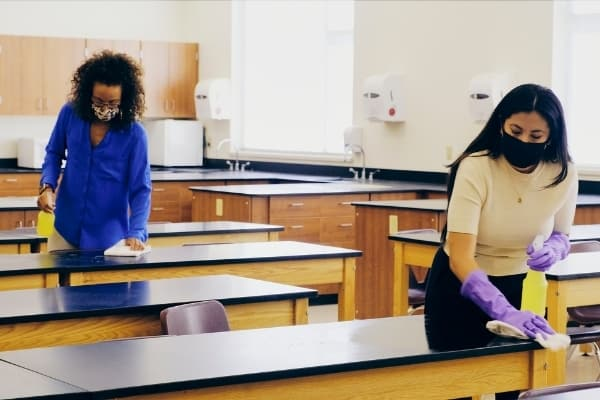 Two ladies disinfecting classroom. Fully managed cleaning service Cambridge