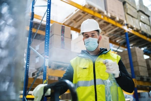 Masked gentleman disinfecting industrial warehouse. Industrial cleaning service Cambridge.