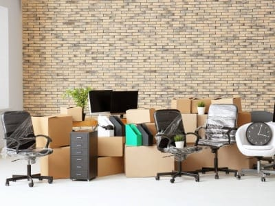 Carton boxes with stuff in empty room. Office move concept. Office clearance service Cambridge.