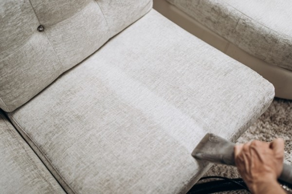 Male worker removing dirt from light sofa with professional vacuum cleaner indoors, closeup/ Upholstery Cleaning service in Cambrigde