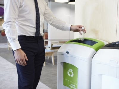 Cleaning services in Cambridge Man in an office throwing plastic bottle into recycling bin. Waste management Cambridge